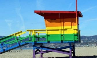 View of a wooden hut painted in rainbow colors standing on a beach.